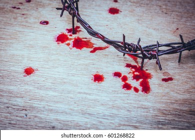 close up of metal Barbed Wire made like the crown of thorns of Jesus with red blood over wooden background with copy space, Christian concept , Easter background