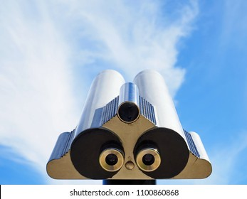 Close up metal binoculars on background viewpoint overlooking the blue sky with clouds. Touristic telescope.