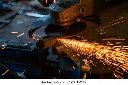 Close up of metal disk grinding steel pipe in factory