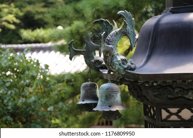 A close up of metal ornaments on traditional Japanese lantern, including bells and mythical creatures shachihoko, half-tigers, half-fishes, with green trees and tile roof in the background