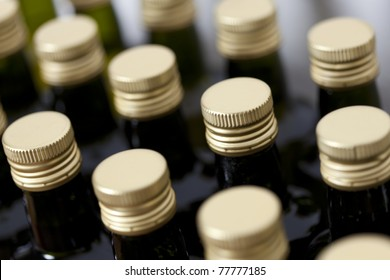 Close up of metal screw caps on dark glass (wine) bottles lined up, top view on white background.