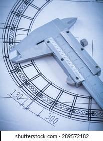Close up of metal trammel caliper on blueprint construction concept.