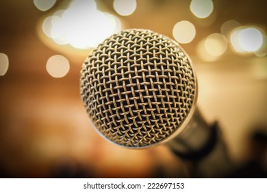 Close up of microphone in concert hall or conference room with lights in background. Macro with extremely shallow dof.