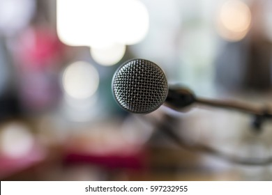 Close up of microphone in concert hall or conference meeting room with blurred abstract lights in background.