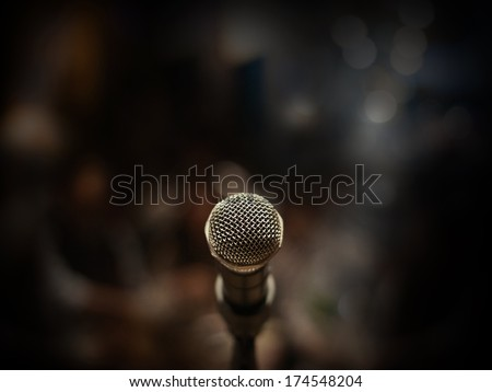 Close up of microphone in concert hall or conference room blur background.