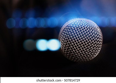 close up microphone with lights in background.