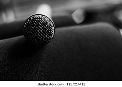 Close up microphone is on a gray background.Microphone for broadcast, karaoke, or on stage recording room. Include meeting.Color tone monochrome.