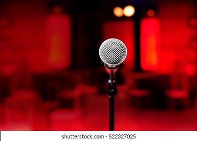 close up of microphone on stage with defocused bokeh lights red colour background