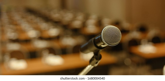 Close up of microphone on stage in meeting room. Blurred background. Microphone, stage, room, class, meeting, greeting concept.