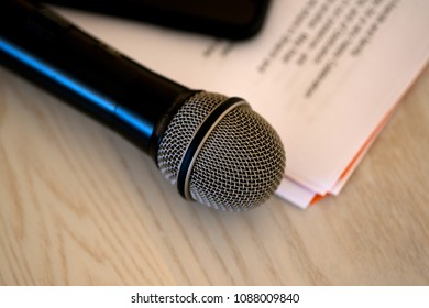 Close up microphone with paper notecards. Concept of speaker preparation to speak. Wedding speech.