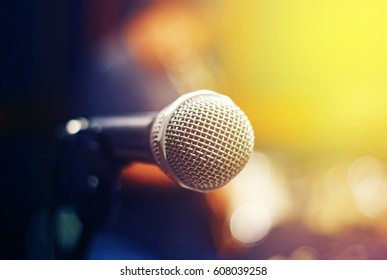 Close up microphone in sound studio with bokeh yellow background.