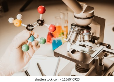 Close up of microscope viewing sample with atom ball and stick molecular model for research, learn, work, solution in chemistry laboratory.