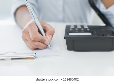 Close up mid section of a businesswoman using telephone while writing on clipboard at desk