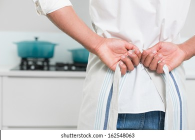 Close up mid section of a young man wearing apron in the kitchen