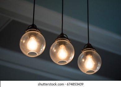 Close up midcentury modern remodeled home dining living room ceiling chandelier with three hanging incandescent illuminated light bulbs in glass globe orbs on black electrical cable with crown molding