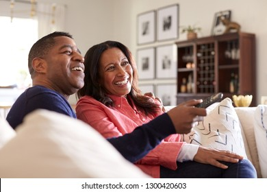 Close up of middle aged African American couple sitting on the sofa in their living room using remote and watching TV, laughing, close up