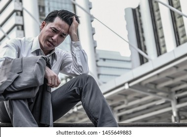 Close up middle aged asian businessman feeling stress and depressed when he jobless from company laid off problems. Economic recession effect concept, copy space.
