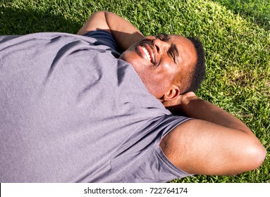 close up of middle aged black man lying on grass in the sunshine