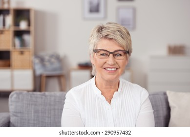Close up Middle Aged Blond Woman with Eyeglasses, Sitting on the Couch and Looking at the Camera with Toothy Smile.
