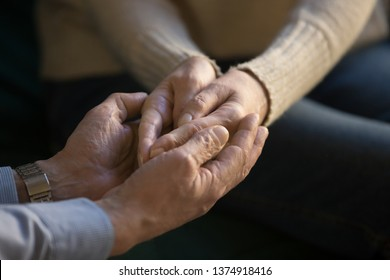 Close up middle aged loving husband holding hands of wife, showing love and support, tenderness, mature couple, family enjoying moment, good relationship, elder man caressing, comforting woman