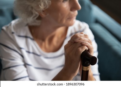 Close up middle aged thoughtful woman holding wrinkled hands on wooden cane, suffering from loneliness. Unhappy older senior grandmother thinking of physical problems, having walking disability.