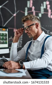 Close up of middle-aged caucasian trader looking focused while sitting in front of computer monitor. Blackboard full of charts and data analyses in background. Stock trading, people concept.