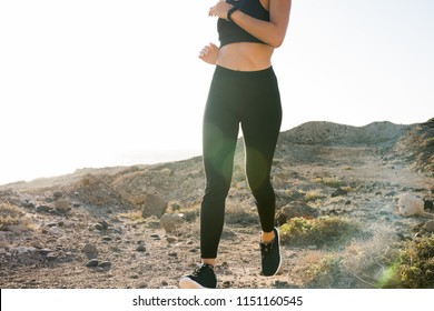 Close up of a midriff of a young woman as she runs through the desert