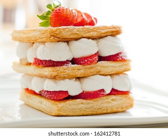 Close up of mille feuille, puff pastry layered with strawberries and whipped cream