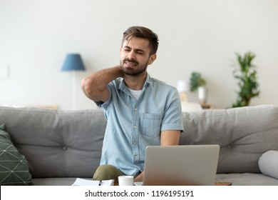 Close up millennial man sitting on couch touching massaging neck. Exhausted tired male suffering from neck pain ache after sedentary work or study at home for a long time feeling unwell and discomfort