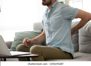 Close up millennial man sitting on couch touching massaging back. Exhausted tired male suffering from back pain ache after sedentary work or study at home for a long time feeling unwell and discomfort