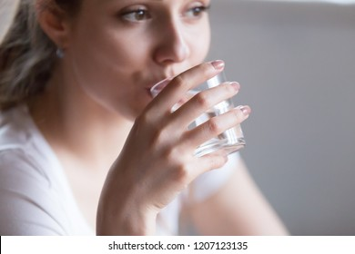 Close up millennial woman holding glass looking away drinking still water, focus on hand. Beautiful healthy pensive female on diet starting day with fresh natural water metabolism acceleration concept