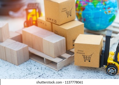 Close up of mini forklift truck that load cardboard box with shopping cart symbol and globe near by. Logistics and transportation management ideas and Industry business commercial concept.