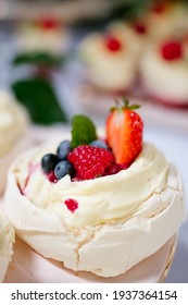 Close up of a Mini Pavlova dessert decorated with blueberry and strawberries on a candy bar, wedding buffet table