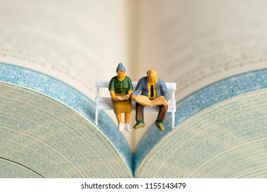 Close up of miniature figures of an elderly couple read book and newspaper on a bench.