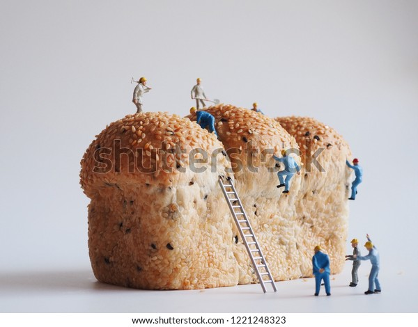 Close up miniature people many of worker man working on whole grain bread background,team work concept.