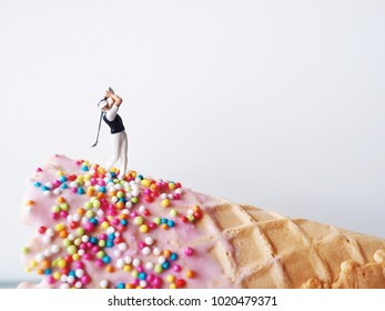 Close up miniature people playing golf on ice cream cone.