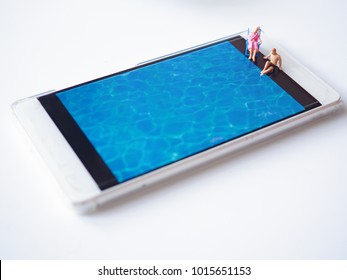 Close miniature people with pool water background in smart phone on white background,vacation time concept.