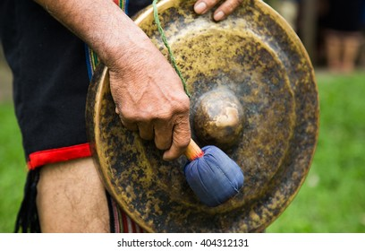 Close up of minority man in traditional dress knocking a copper gong within a holiday
