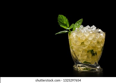 Close up of a mint julep with served over crushed ice and garnished with a fresh mont sprig isolated on a black background