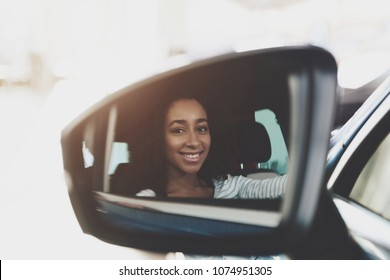 Close up mirror. African american family at car dealership. Mother sitting on driver's seat of new blue car.