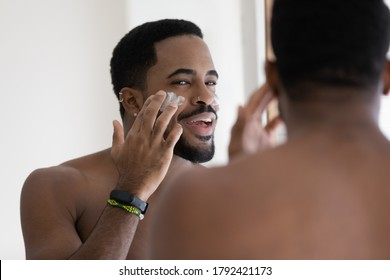 Close up mirror reflection positive African American handsome young man applying moisturizing face cream or aftershave lotion, standing in bathroom at home, enjoying skincare procedure