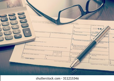 Close up of miscellaneous income form on table with calculator and glasses