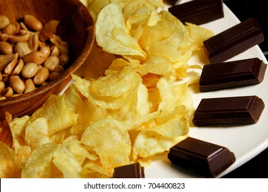 Close up of the mix beer snacks on wooden background. Potato chips, roasted ,salted peanuts and chocolate