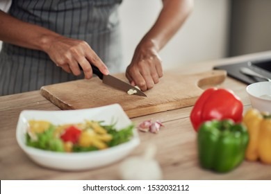 Close up of mixed race woman in apron standing in domestic kitchen and cutting garlic.