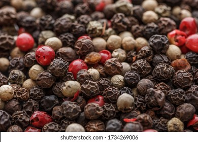 Close up of Mixted multi coloured peppercorns. white, black and green peppercorns macro background.Mixed peppercorns red black and white in bowl - Close-up.