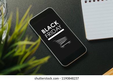 Close up of mobile phone with Black Friday marketing design in the screen, on a black business table.