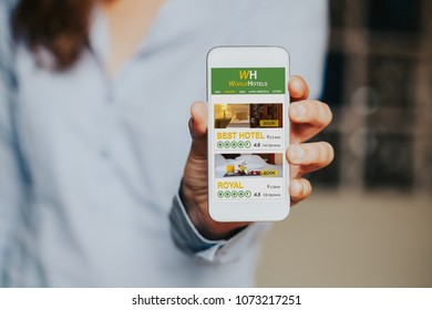 Close up of mobile phone with a Hotel booking website app in the screen, while white caucasian woman is holding it in the hand.