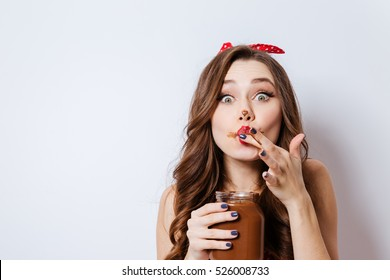 Close up model in underwear eating chocolate cream from jar. girl so pleased. liking her finger. isolated gray background