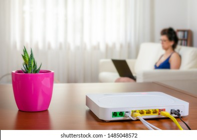 Close up of a modem router on a table in a living room with a woman using a laptop while sitting on the sofa in background