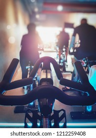 Close up modern Bike with blurred row of man and woman exercise bikes. Fitness cycling indoor concept.